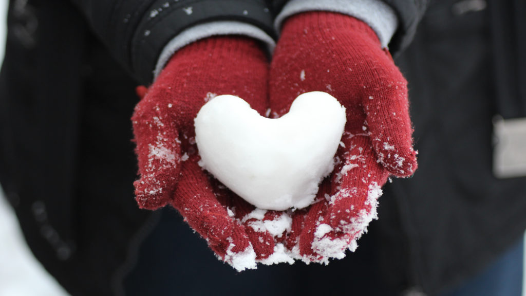 snow heart held by red gloved hands
