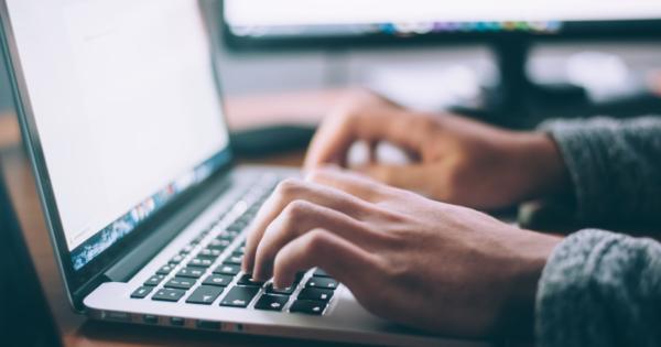 man typing at laptop on desk